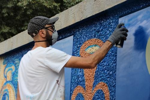 Artistas realizando los murales ganadores del concurso de arte urbano